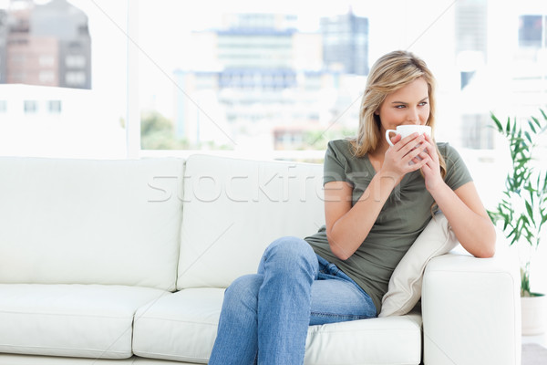 A woman sitting on the couch with a mug up to her nose, legs crossed and looking to the side. Stock photo © wavebreak_media