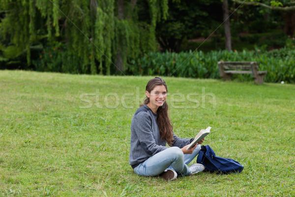 Souriant lecture livre séance herbe Photo stock © wavebreak_media