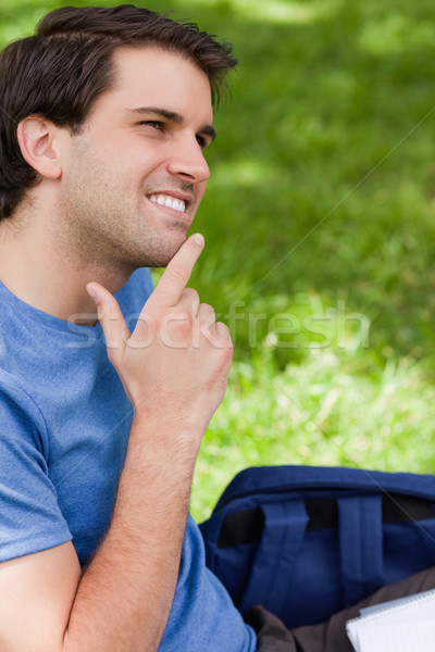 Young smiling man placing his finger on his chin while sitting in a park Stock photo © wavebreak_media