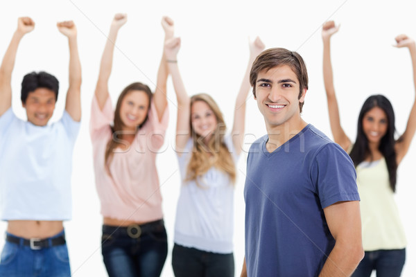 Smiling man with people behind him raising their arms against white background Stock photo © wavebreak_media
