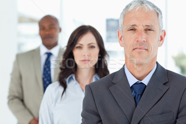 Mature manager standing upright and followed by two serious employees Stock photo © wavebreak_media