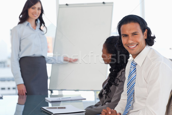Stock photo: Smiling young employee listening to the presentation given by an executive