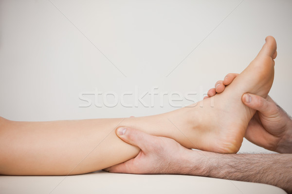 Chiropodist holding the calf of a patient in his medical room Stock photo © wavebreak_media