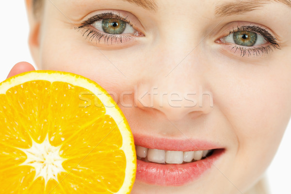 Close up of a woman placing an orange near her lips against white background Stock photo © wavebreak_media
