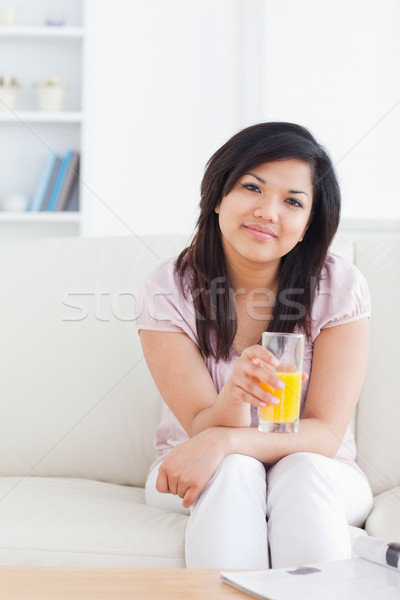 Сток-фото: женщину · сидят · диван · стекла · апельсиновый · сок
