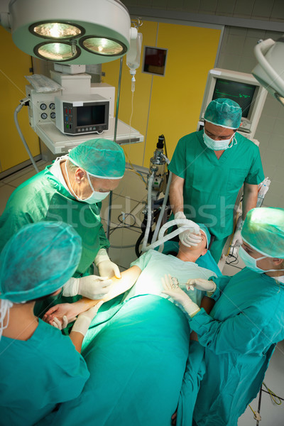 Surgeon and his team working on a patient in a surgical room Stock photo © wavebreak_media
