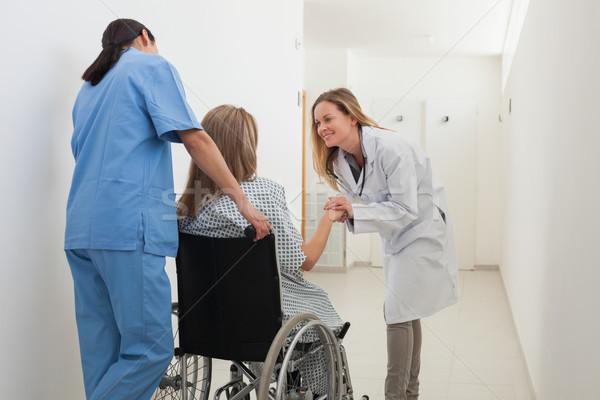 Doctor talking to patient in wheelchair while nurse is pushing in hospital corridor Stock photo © wavebreak_media
