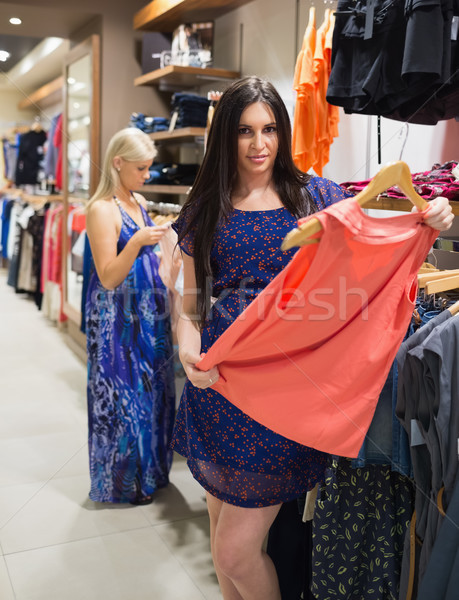 Woman looking at clothes and smiling in clothes store Stock photo © wavebreak_media