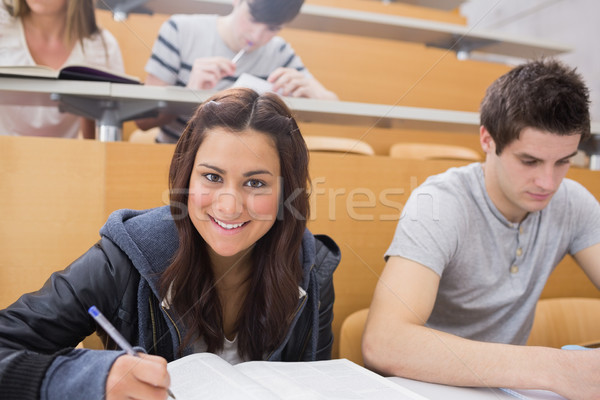 Student writing at the lecture hall while smiling with classmate Stock photo © wavebreak_media
