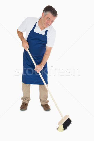 Happy man in blue apron sweeping floor Stock photo © wavebreak_media