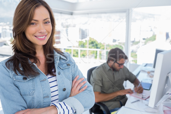 Woman smiling in creative office with arms crossed Stock photo © wavebreak_media