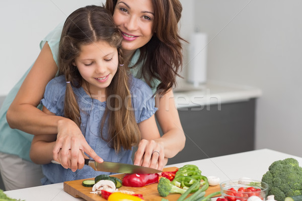 Smiling woman with daughter chopping vegetables in kitchen Stock photo © wavebreak_media