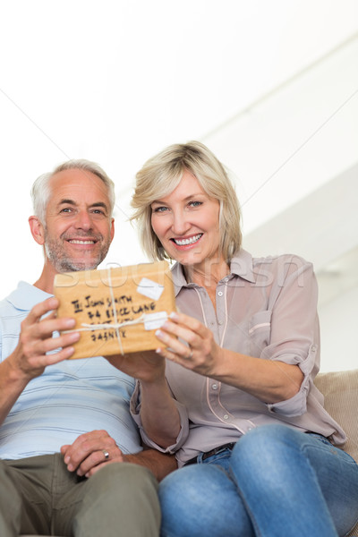 Smiling woman surprising mature man with a gift on sofa Stock photo © wavebreak_media