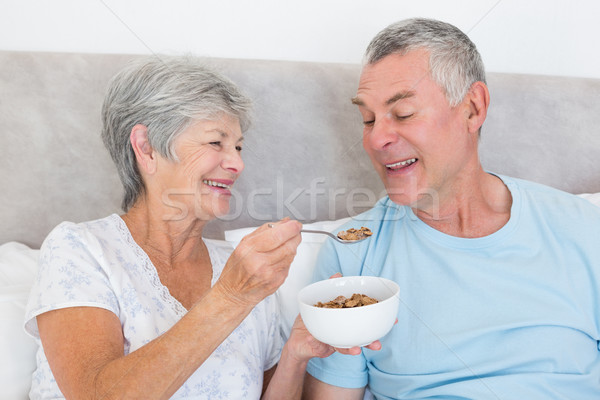 Senior woman feeding cereals to husband Stock photo © wavebreak_media