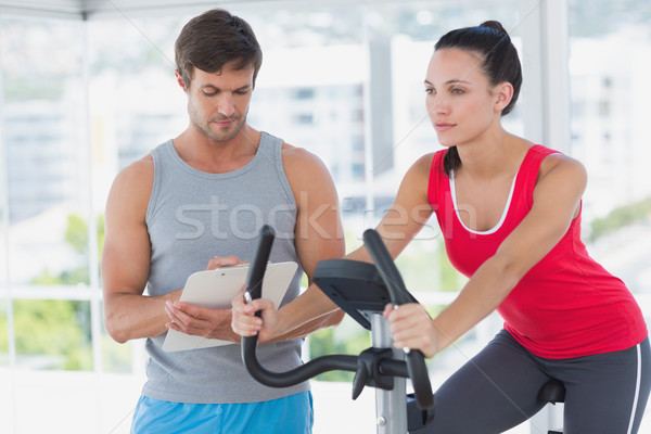 Woman with male instructor working out at spinning class Stock photo © wavebreak_media
