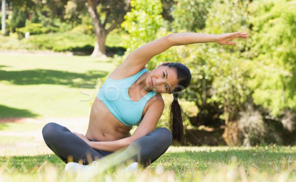 Stock photo: Healthy and beautiful woman doing stretching exercise in park