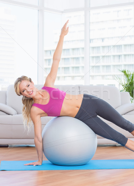 Happy fit blonde doing side plank with exercise ball Stock photo © wavebreak_media