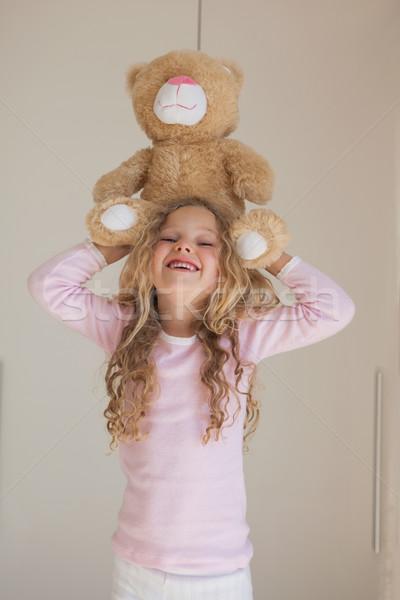 Portrait of happy girl holding stuffed toy over head Stock photo © wavebreak_media