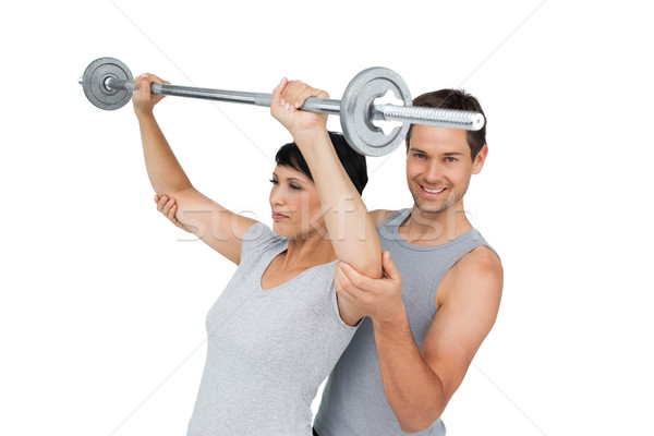 Personal trainer helping woman with weight lifting bar Stock photo © wavebreak_media