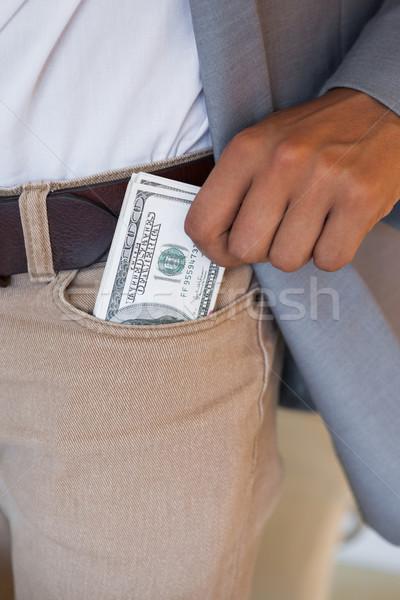 Dodgy businessman pocketing wad of dollars Stock photo © wavebreak_media