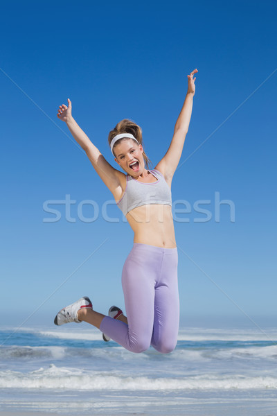 Stock photo: Sporty happy blonde jumping on the beach