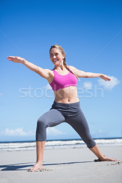 Happy fit blonde standing in warrior position on the beach Stock photo © wavebreak_media