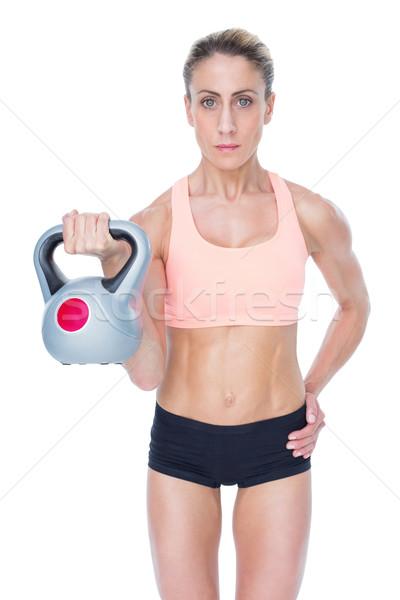 Serious female crossfitter lifting kettlebell  Stock photo © wavebreak_media