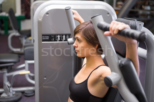 Stock photo: Athletic brunette using weights machine for arms