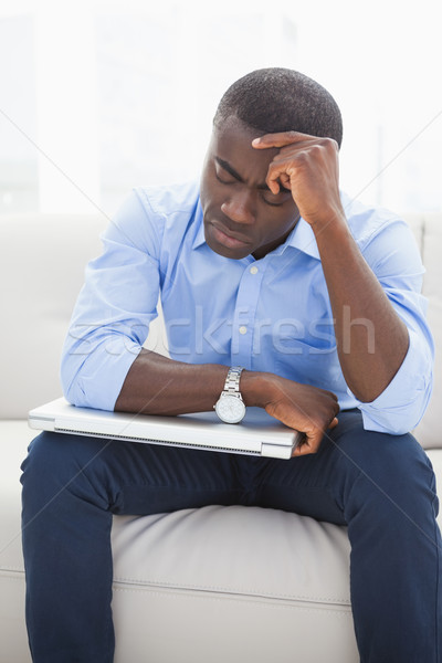 Stressed businessman getting a headache holding his laptop Stock photo © wavebreak_media