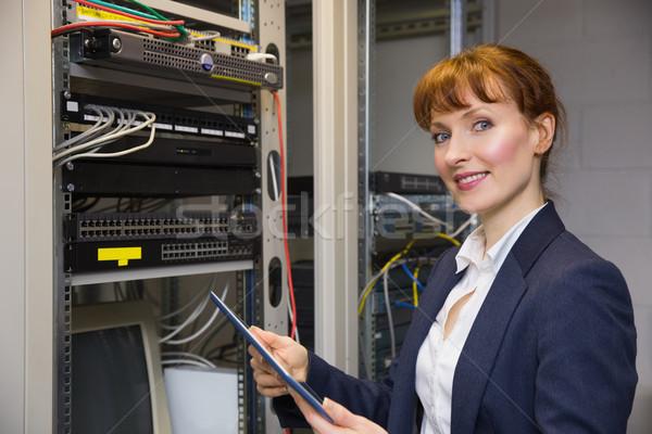Pretty technician using tablet pc while fixing server Stock photo © wavebreak_media