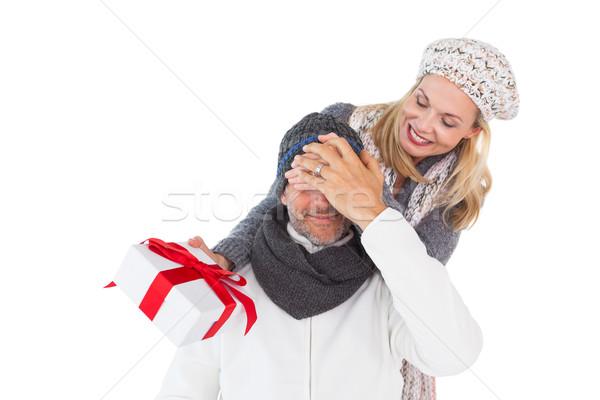 Happy woman holding gift while covering husbands eyes Stock photo © wavebreak_media