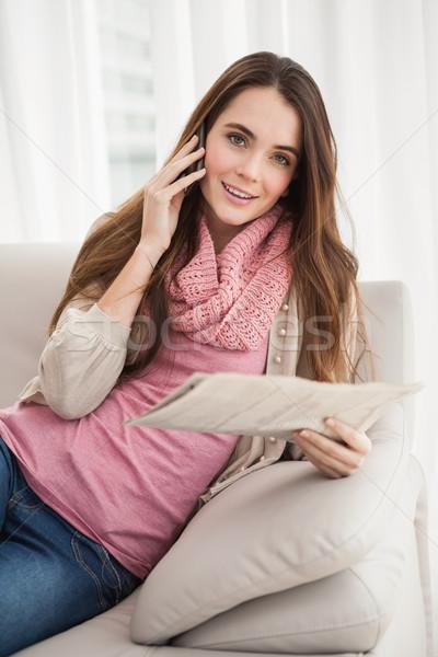 Pretty brunette on the phone holding newspaper Stock photo © wavebreak_media