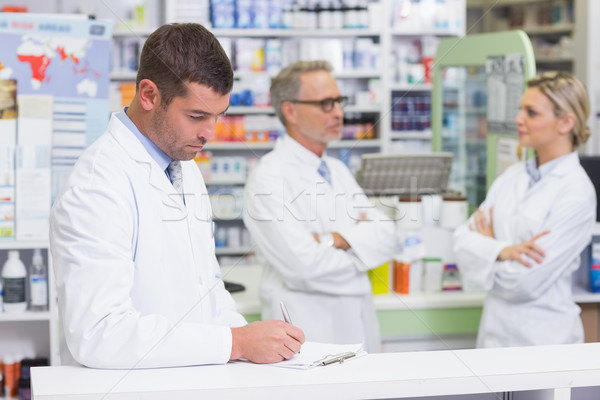 Pharmacist in lab coat writing a prescription Stock photo © wavebreak_media