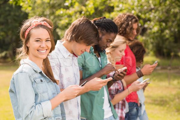 Boldog barátok park telefonok napos idő nő Stock fotó © wavebreak_media