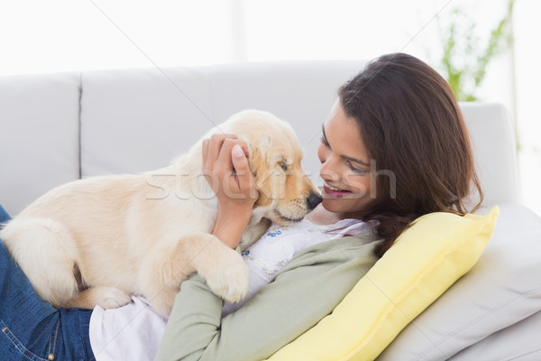 Woman playing with puppy while lying on sofa Stock photo © wavebreak_media