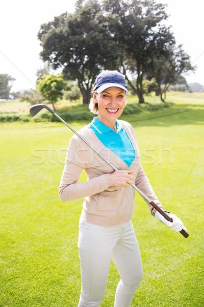 Vrouwelijke golfer permanente club glimlachend Stockfoto © wavebreak_media