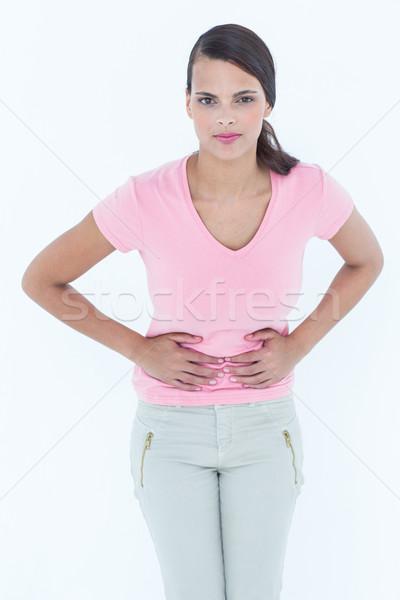 Nő gyomor fájdalom néz kamera fehér Stock fotó © wavebreak_media