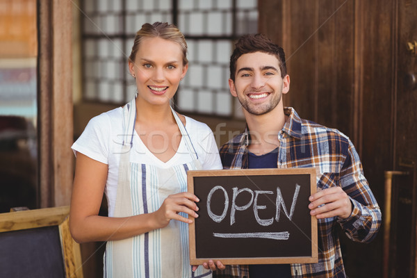 Smiling waitress and man holding chalkboard with open sign  Stock photo © wavebreak_media