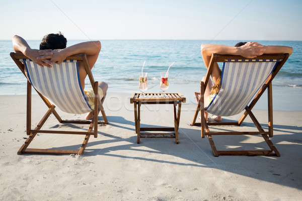 Couple relaxing on lounge chairs at beach Stock photo © wavebreak_media