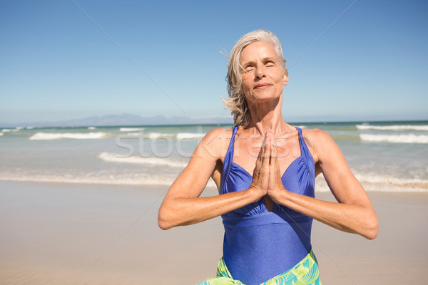 Close up of senior woman with hands clasped standing at beach Stock photo © wavebreak_media