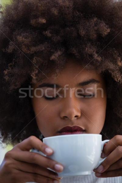 Young woman with frizzy hair smelling coffee Stock photo © wavebreak_media