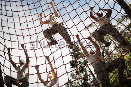 Group of fit woman climbing a net during obstacle course training Stock photo © wavebreak_media