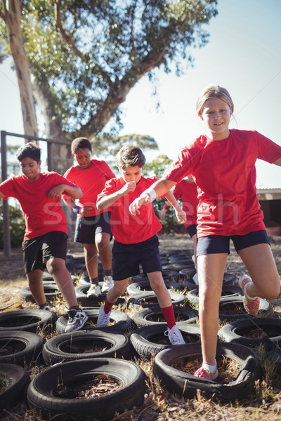 Kids running over tyres during obstacle course training Stock photo © wavebreak_media
