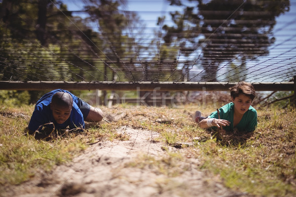 Kids crawling under the net during obstacle course Stock photo © wavebreak_media