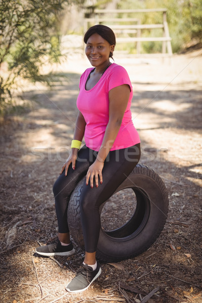 Portrait of smiling woman relaxing on huge tyre during obstacle course Stock photo © wavebreak_media