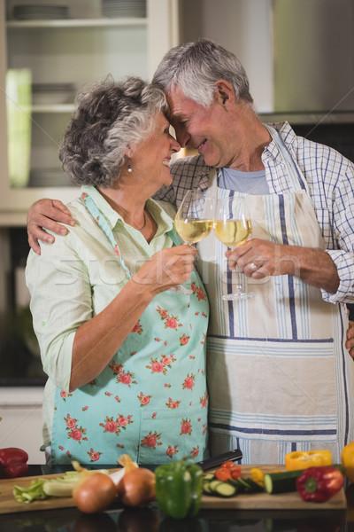 Happy senior couple toasting wine glasses together in kitchen Stock photo © wavebreak_media