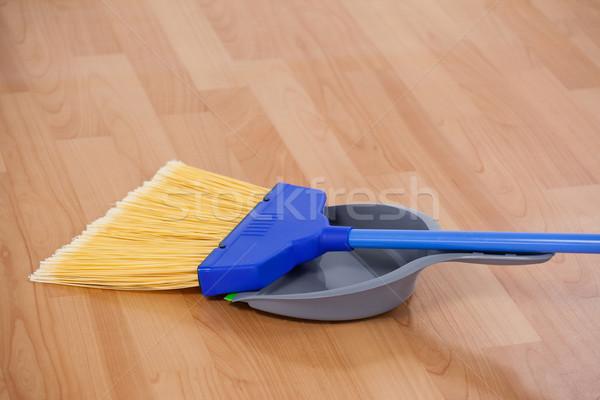 Sweeping broom with dustpan on wooden floor Stock photo © wavebreak_media