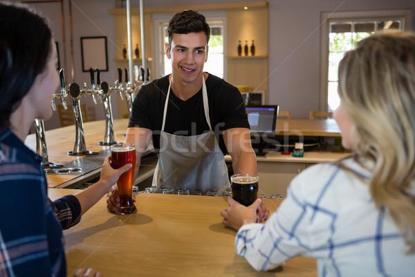 Bartender serving drinks to young friends Stock photo © wavebreak_media