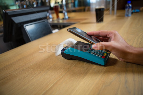 Cropped hand of customer making contactless payment Stock photo © wavebreak_media