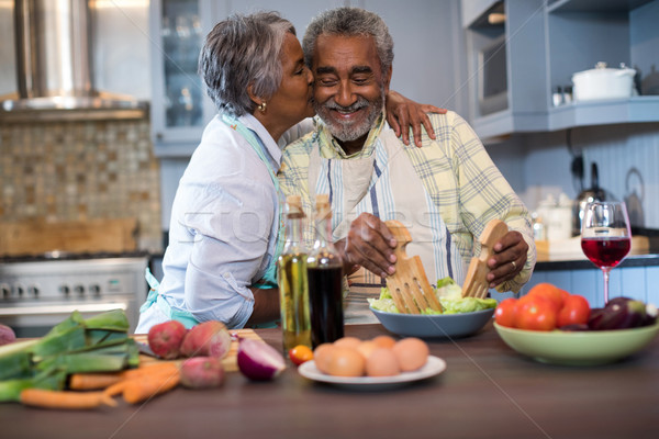 Senior woman kissing man while preparing food Stock photo © wavebreak_media